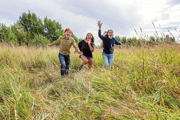 Группа из трех друзей, мальчика и двух девочек, бегающих и веселящихся вместе на открытом воздухе