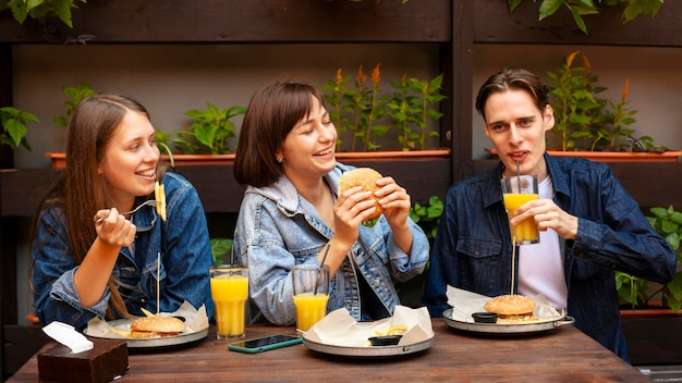 Группа трех друзей, едящих гамбургеры