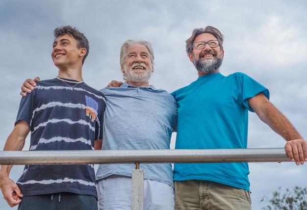 Группа из трех поколений семьи обнимаются и улыбаются на открытом воздухе, дедушка и бабушка, сын и внук вместе