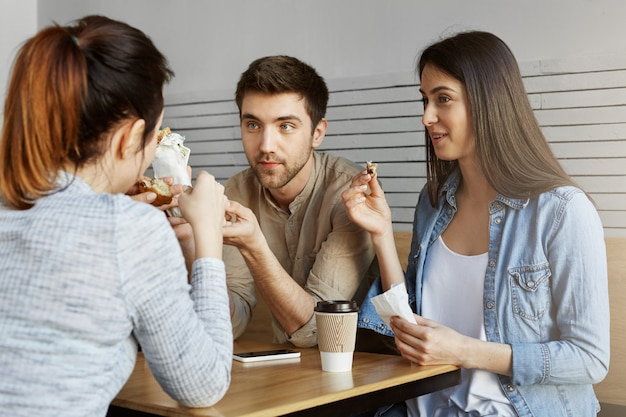 大学の食堂に座って、昼食をとり、昨日の試験について話している3人のハンサムな学生のグループ。大学生活。