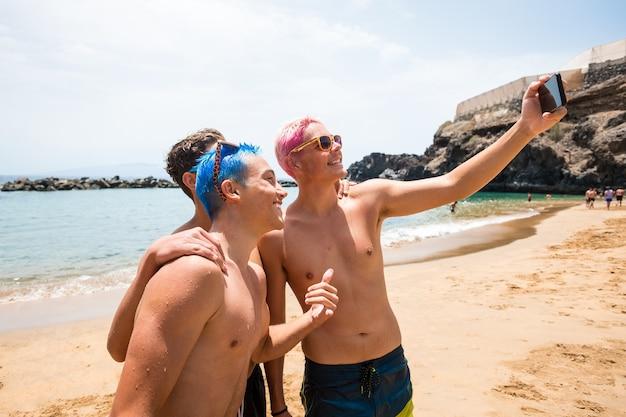 3명의 행복하고 쾌활한 십대 소년들이 해변에서 함께 셀카를 찍는 카메라를 보며 웃고 즐기고 있습니다.