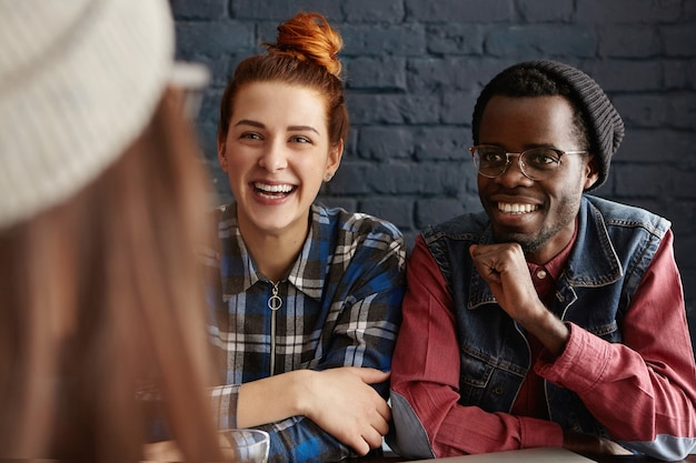 Группа трех счастливых студентов, весело проводящих время в помещении