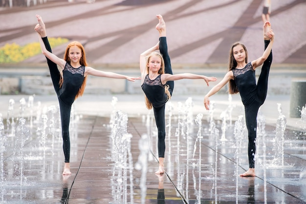 꽉 끼는 검은색 정장을 입은 세 명의 작은 발레리나 그룹이 더운 날 도시 분수를 배경으로 춤을 춥니다.