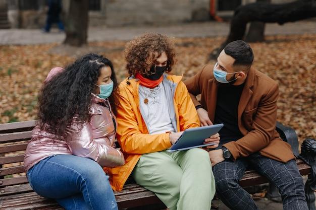 ベンチに座ってデジタルタブレットを使用している医療用マスクの3人の多文化の人々のグループ。秋の公園でリラックスした若い男性と女性の友人。