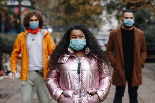 医療用マスクで街の通りでポーズをとる3人の多文化の人々のグループ。社会的距離、検疫および対策の概念。