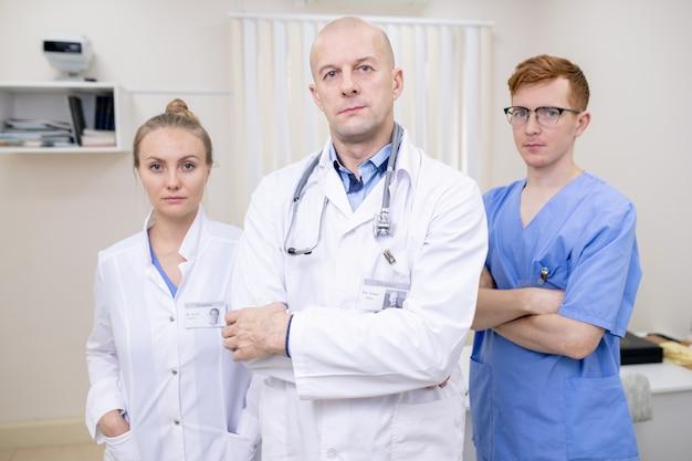 Группа из трех серьезных молодых и зрелых профессиональных клиницистов в униформе