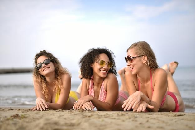 ビーチで笑顔の若い女性3人のグループ-幸せの概念