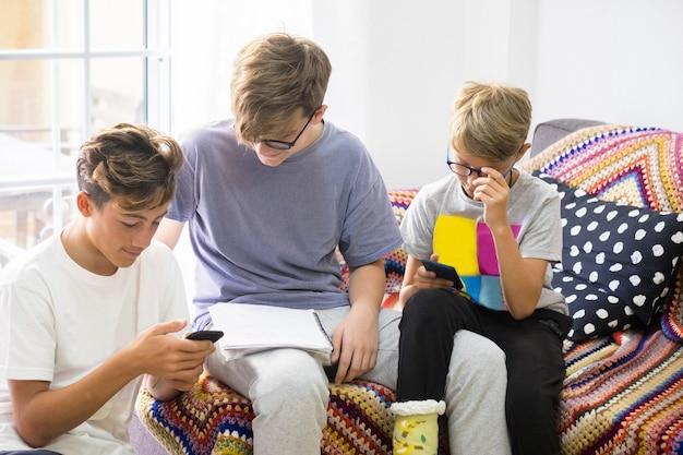 Группа из трех подростков, сидящих на диване, смотрящих на телефон и проверяющих свою домашнюю работу, проверяют, правильно ли это