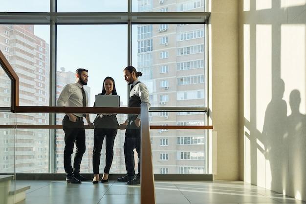 회의에서 노트북에서 프레젠테이션을 논의하는 동안 큰 창 옆에 서있는 세 젊은 우아한 관리자 또는 에이전트 그룹