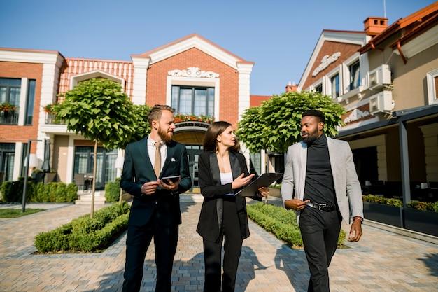 3つの若い多民族のビジネス人々のグループ、アフリカ人と白人男性と女性、お互いに話して、屋外で歩く