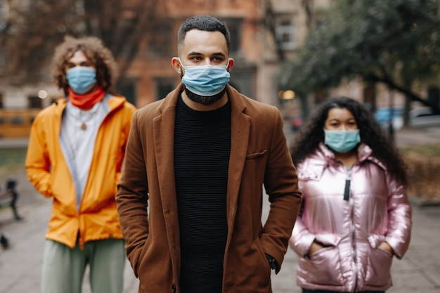 屋外の距離に立って、医療用保護マスクを着用している3人の若者のグループ。検疫対策の概念。