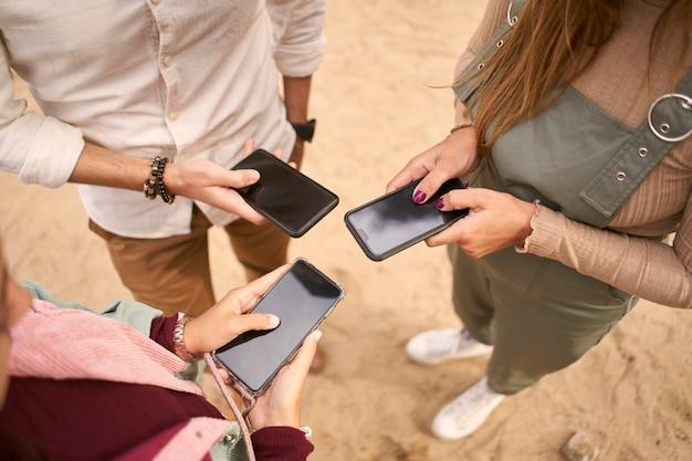 スマートフォンを一緒に使う3人の若者のグループ。