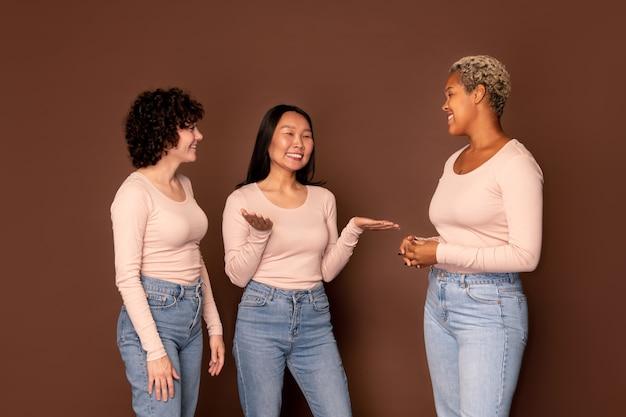 Группа из трех молодых улыбающихся женщин в белых пуговицах и синих джинсах, болтающих о своих планах или любопытных вещах, которые произошли недавно