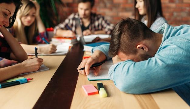 Группа усталых старшеклассников готовится к экзаменам.