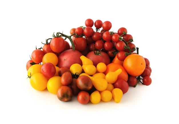 白い背景の上の異なる色と品種のトマトのグループ