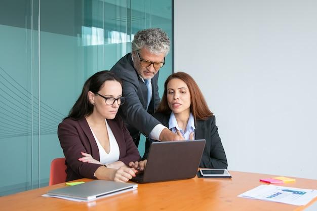ノートパソコンでプロジェクトのプレゼンテーションを見て話し合うトップマネージャーのグループ、ディスプレイを指す男性のエグゼクティブ、詳細を説明する女性のマネージャー