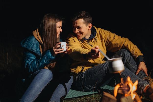 Группа друзей-туристов возле палатки, готовит ужин у костра