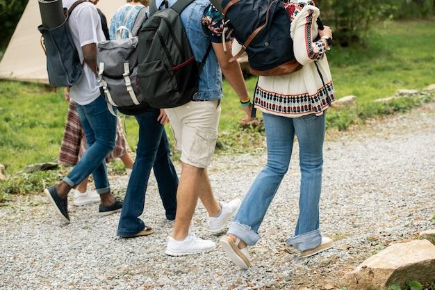 Группа туристов с рюкзаками, идущих по галечной дорожке во время регистрации в кемпинге