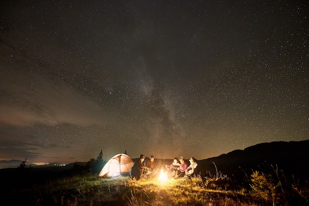Группа туристов с гитарой у горящего костра под темным звездным небом с созвездием млечный путь.