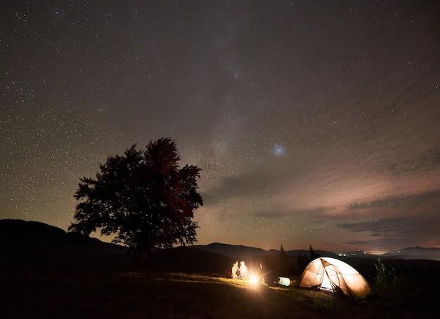은하수 별자리와 어두운 별이 빛나는 하늘 아래에서 모닥불을 태워 기타와 함께 관광객의 그룹입니다.