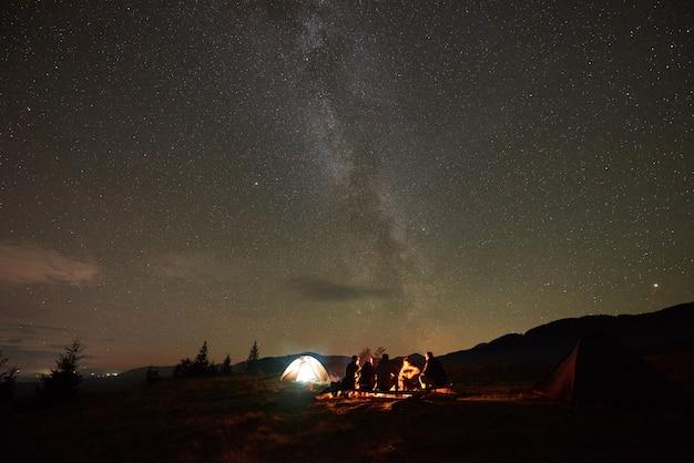 天の川の星座で暗い星空の下で焚き火を燃やすことによってギターを持っている観光客のグループ。