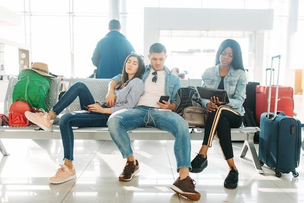 空港で出発の遅延を待っている荷物を持つ観光客のグループ。