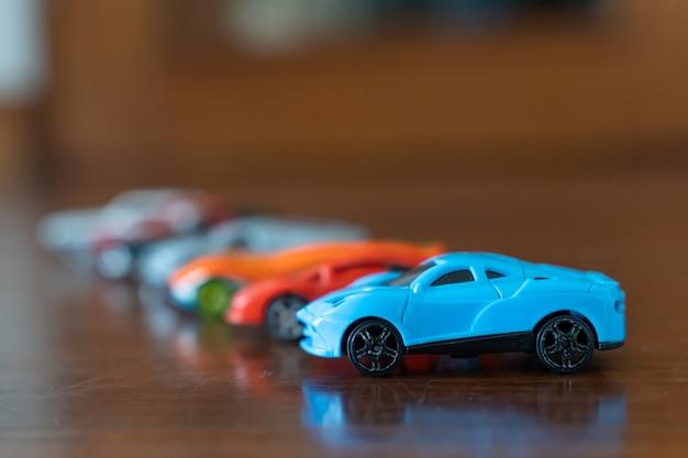 Группа игрушечных машинок разного цвета с синим спортивным автомобилем на передней панели.