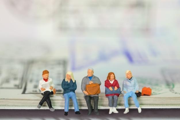 パスポートに座って待っている旅行者ミニアルルフィギュアの人々のグループ