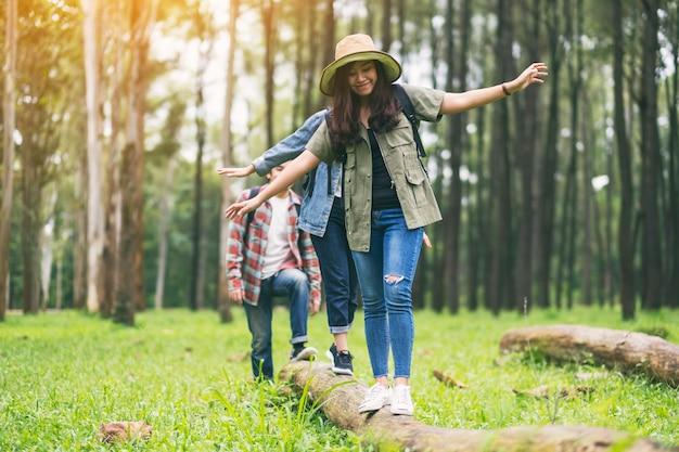 숲에서 하이킹하는 동안 통나무 위를 걷는 여행자의 그룹