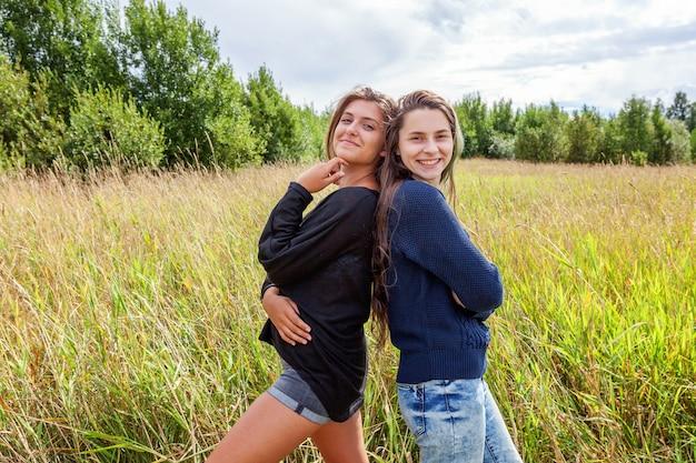 抱き合って踊り、屋外の自然の中で一緒に楽しんでいる2人のガールフレンド姉妹のグループ