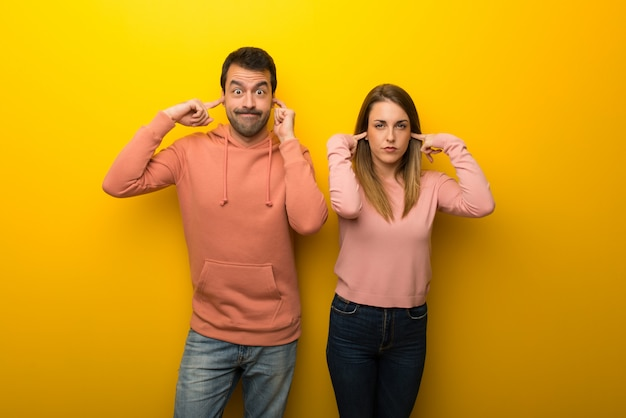 手で両耳を覆っている黄色の背景に二人のグループ
