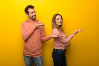 Group of two people on yellow background extending hands to the side