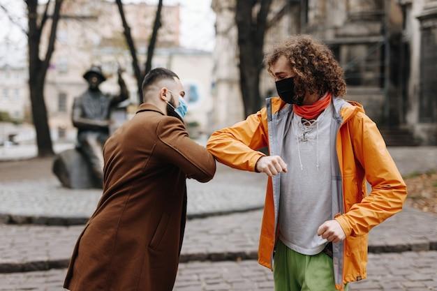屋外に立って肘でお互いに挨拶する医療用保護マスクの2人の若い男性のグループ。検疫時間の概念。
