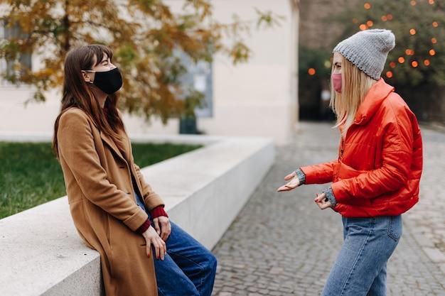 通りで笑顔で話しているカジュアルな暖かい服を着た2人の若い女性のグループ。パンデミックの時期に保護フェイスマスクを着用した幸せな友達。