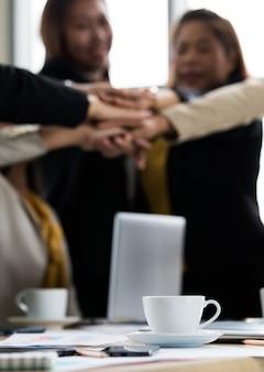 Группа неопознанных неузнаваемых успешных женщин-предпринимателей в повседневном бизнесе носит стоя, держась за руки вместе, расширяет возможности в качестве соглашения о совместном партнерстве в офисе компании.