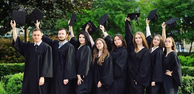 Группа выпускников вузов или колледжей в черных халатах подняли руки с квадратными шапками выпускников и рады выпускному.