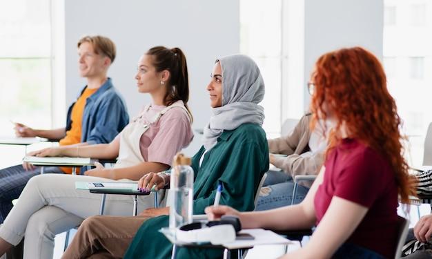 Группа студентов университета, сидя в классе в помещении, учится.