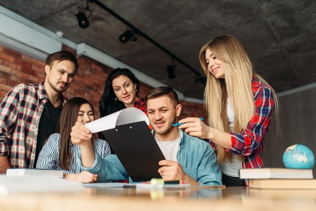 Группа студентов университета вместе смотрит на ноутбук. люди с компьютером ищут информацию в интернете, командная работа, совместный проект