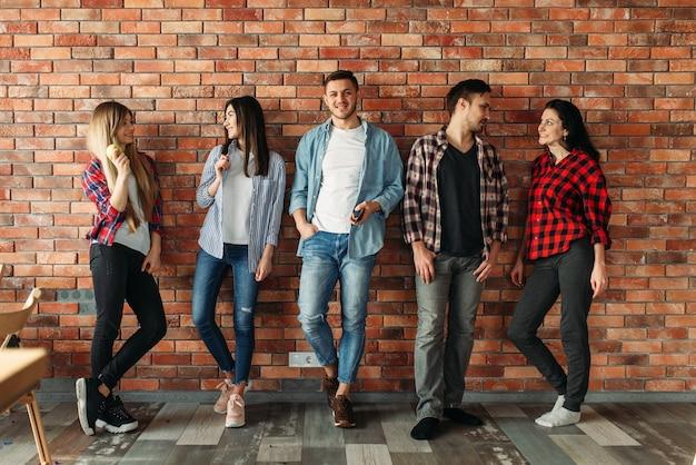 Группа студентов университета, стоящих у кирпичной стены. позы школьников