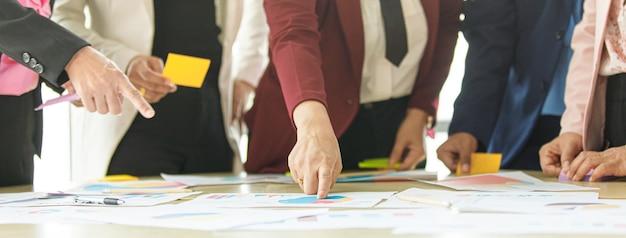 알아볼 수 없는 여성 사업가 그룹이 업무용 책상에서 함께 브레인스토밍을 하고, 손가락을 가리키고, 분석 데이터 차트와 그래프를 자신감을 갖고 팀 내 지식 교환으로 가득 차 있습니다.