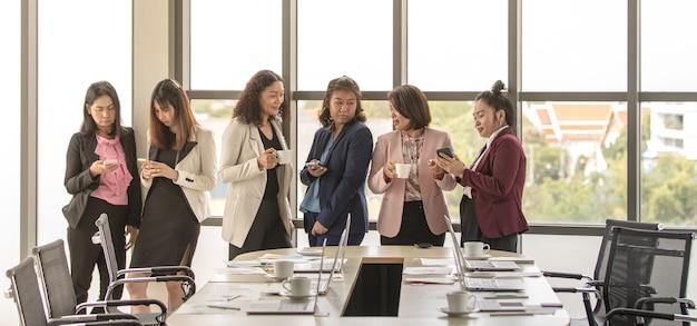 Группа неузнаваемых деловых женщин, стоящих вместе в офисе во время перерыва. работа в команде сотрудников женского пола, расслабляющаяся и легкая при использовании смартфона и питье кофе.