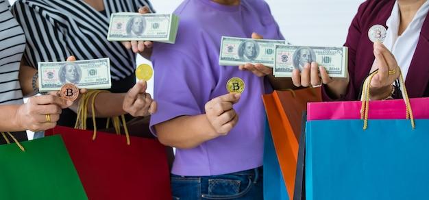 암호 화폐 동전과 달러 지폐와 쇼핑백을 손에 들고 있는 알아볼 수 없는 여성 그룹. 현대인의 실생활에서 사용하는 암호화폐 지불 및 디지털 화폐의 개념.