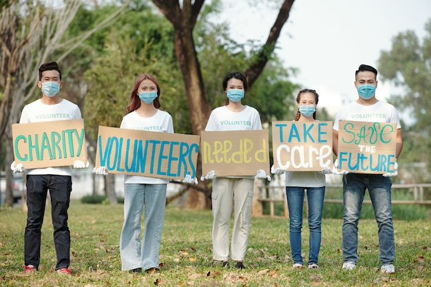 Группа волонтеров в защитных масках, стоящих на улице с плакатами, призывающих людей присоединиться к благотворительной организации