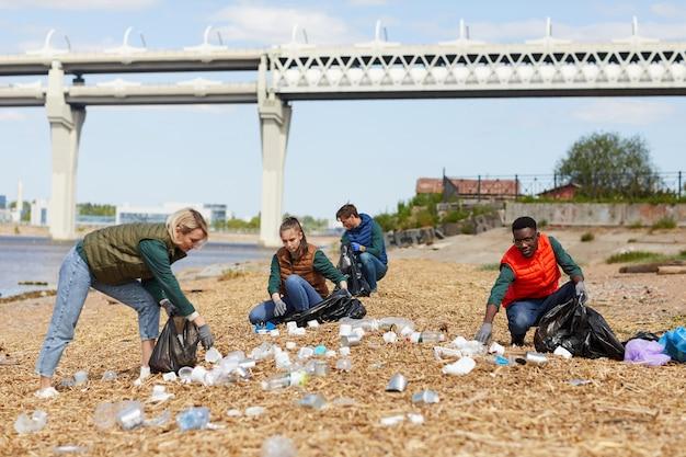 Группа волонтеров собирает мусор на берегу реки на природе