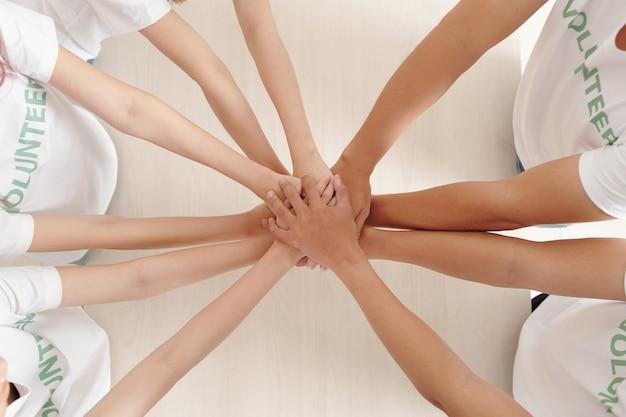 화합과 지원을 표현하기 위해 테이블 위에 손을 얹고 있는 자원 봉사자 그룹, 위에서 보기