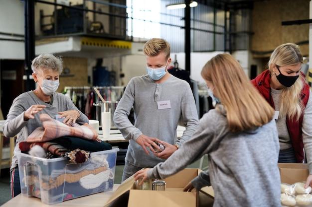 Группа волонтеров, работающих в общественном центре благотворительных пожертвований, продовольственном банке и концепции коронавируса.