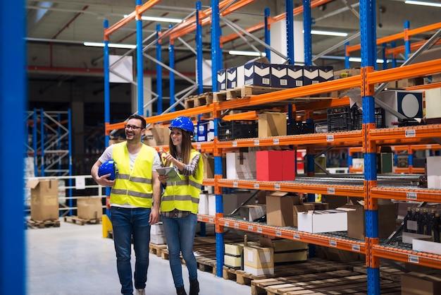 패키지와 상품이있는 높은 선반 사이의 통로에서 깨어있는 안전모와 반사 재킷을 입고있는 창고 작업자 그룹