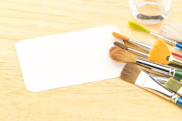 Группа акварельной кисти и пустой белой бумажной карточкой на деревянном столе