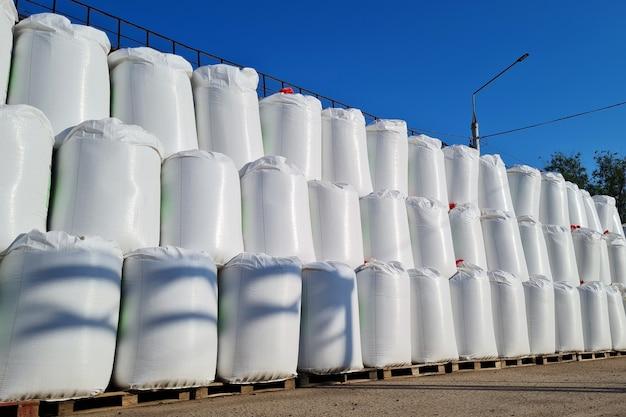 Группа белых больших мешков с химическими удобрениями на складе на открытом воздухе стек мешков в 3 ряда на открытом воздухе на фоне голубого неба в солнечный день