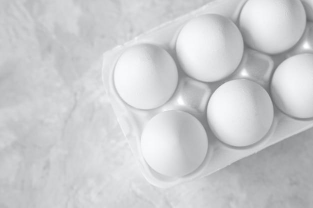 Группа белых яиц в пакете, серый фон, место для текста. селективный фокус, вид сверху.